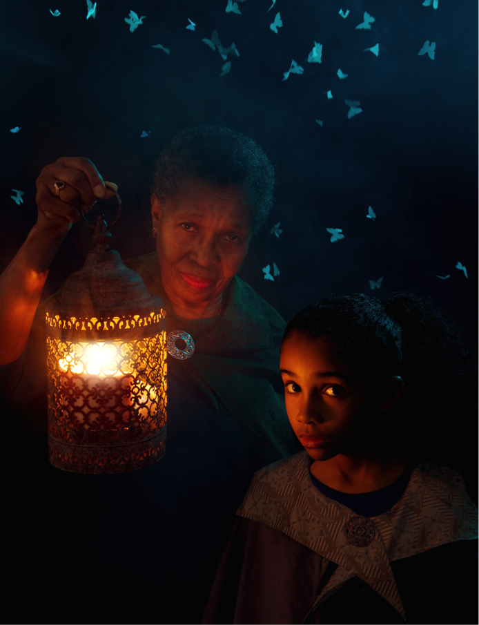 A studio flash unit was used to backlight the falling paper moths, but the pulse of light wasn't brief enough to freeze them completely. This was actually intentional, since the blurred edges of the ethereal moths help convey a timeless fairy tale feeling. A story of a woman and her granddaughter lost in some mysterious place, their way guided by some magical moths. Or something. The interior of the lantern was lit by a 430EX III RT in radio slave mode. An orange gel, a cylinder of paper, and some bubble wrap plastic simulated a candle. At camera left, a studio flash unit, with a blue-gelled gridded dish was used for foreground fill. A blue-gelled studio flash unit on a tall light stand was used to simulate moonlight and outline the models' hair and shoulders. Barn doors were used to pre-vent spill onto the black backdrop paper. Finally, moths cut from vellum paper were shaken down from a tray above and behind the models.